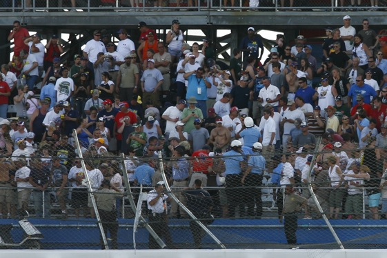 Spectators look on after Carl Edward's crash damaged the fence and injured fans. (RacinToday.com photo by David Vaughn)