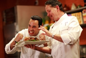 IndyCar Series star Helio Castroneves hams it up as world-renown chef Stephan Pyles presented a roasted chicken.