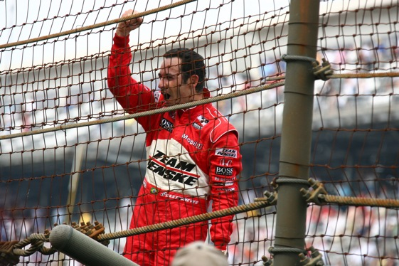 2009 Indianapolis 500 winner Helio Castroneves climbs the fence and waves to his fans. (IMS Photo by  Bret Kelley)