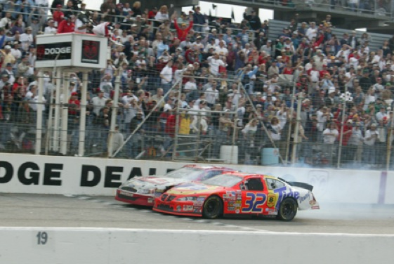 Ricky Craven has inside position and a couple of inches on Kurt Busch as they hit the finish line at Darlington in 2003. And the crowd goes wild. (Photo courtesy of Darlington Raceway)