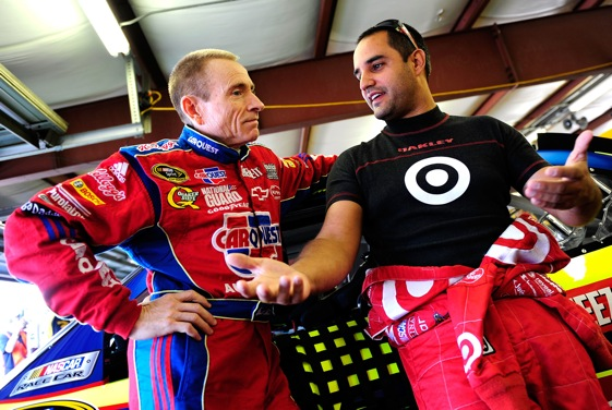 Mark Martin and Juan Pablo Montoya share thoughts in the New Hampshire garages. (Photo by Rusty Jarrett/Getty Images for NASCAR)