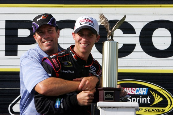Denny Hamlin gets a bear hug from his team president, J.D. Gibbs, following emotional victory at Pocono. (Photo by Chris Trotman/Getty Images for NASCAR)