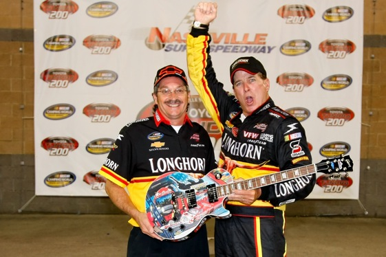 Ron Hornaday Jr. and crew chief Rick Ren display the Sam Bass-painted guitar/trophy that some drivers value so highly. (Photo by Jason Smith/Getty Images for NASCAR)