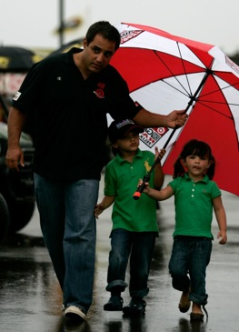 Juan Pablo Montoya walks in the rain with his children Sebastian and Paulina.  (Photo by Todd Warshaw/Getty Images for NASCAR)