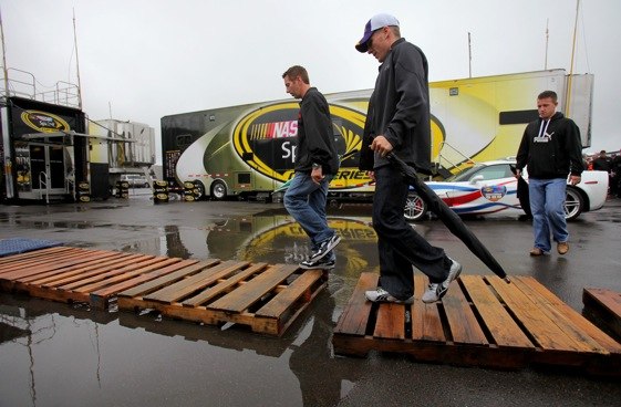 Sprint Cup drivers Greg Biffle and Jamie McMurray cross a bridge over troubling waters in the garages at Pocono on Sunday. The race has been rescheduled to Monday. (Photo by Doug Pensinger/Getty Images)