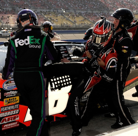 An ill Kyle Busch is pulled from his car during a pit stop in Saturday's Nationwide race. Getting in is Denny Hamlin.