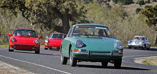 A line of Porsches do what they do best – hit a curve on a beautiful stretch of country road.
