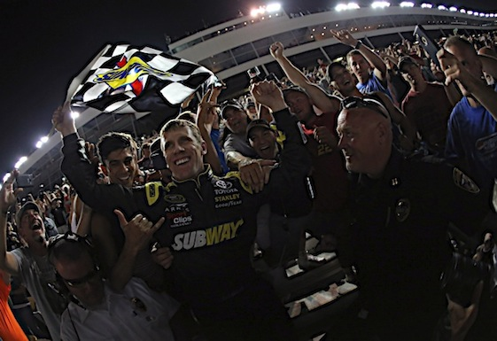 Carl Edwards celebrates his victory in the Coca-Cola 600 with fans in the stands at Charlotte Motor Speedway on Sunday night. Edwards' victory capped an impressive couple of weeks for his Joe Gibbs Racing team.  (RacinToday/HHP photo by Andrew Coppley)