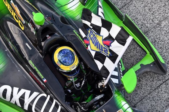Sebastien Bourdais takes a victory lap with the checkered flag at the Milwaukee Mile on Sunday.