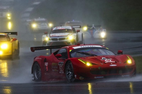 A Ferrari 458 Italia snakes its way through a rain-soaked corner at Road Atlanta.