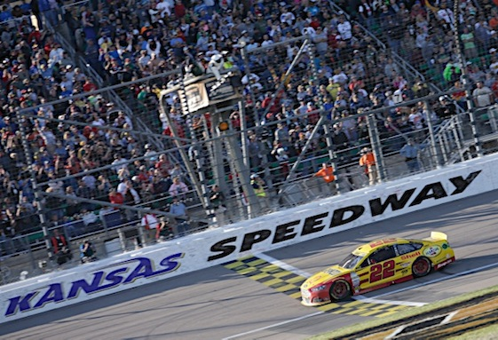 Joey Logano takes the checkered flag at Kansas Speedway on Sunday. A late race bump to leader Matt Kenseth secured the win. (RacinToday/HHP photo by Harold Hinson)
